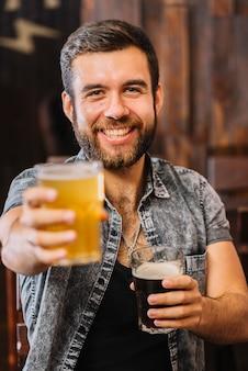 Retrato de um homem feliz segurando copos de rum e cerveja