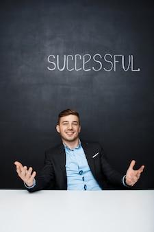 Retrato de um homem feliz sobre placa preta com texto bem sucedido