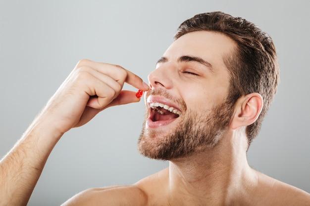 Retrato de um homem feliz, tomando uma cápsula vermelha