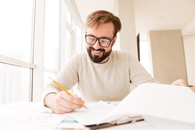 Retrato de um homem feliz trabalhando com documentos