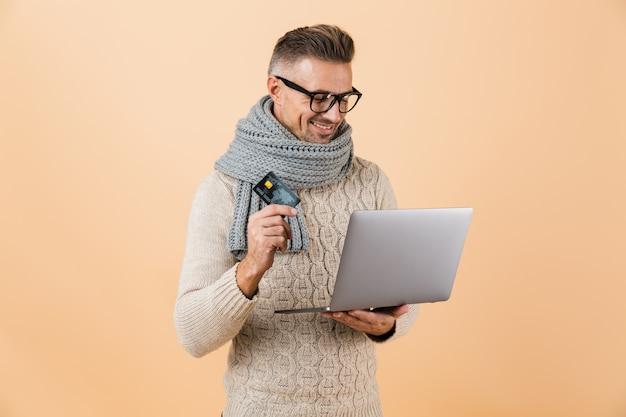 Retrato de um homem feliz, vestido com um suéter e um lenço, em pé, isolado sobre uma parede bege, segurando um laptop e mostrando um cartão de crédito de plástico
