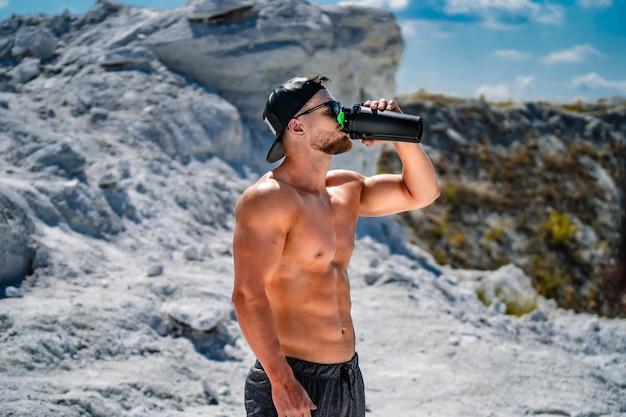 Retrato de um homem fisiculturista bonito halfnacked em copos e uma tampa com uma garrafa de água.
