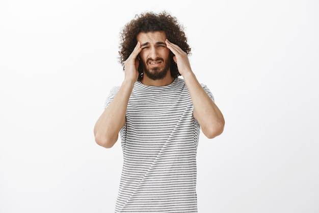 Retrato de um homem fofo questionado e sem foco em uma camiseta listrada, apertando os olhos e segurando as têmporas, tentando se concentrar, tendo dor de cabeça ou enxaqueca