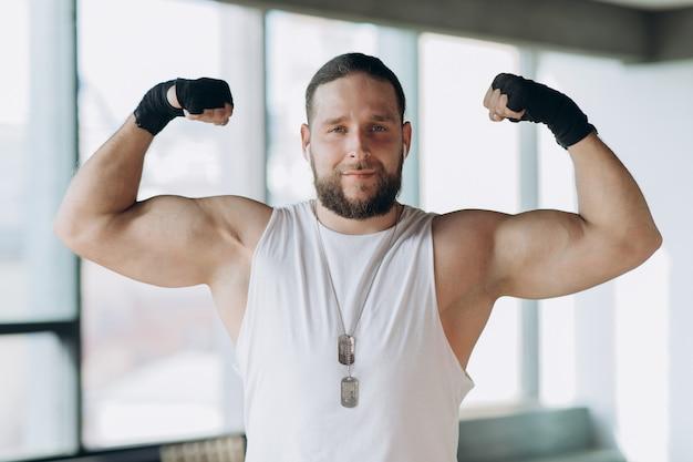 Retrato de um homem forte e musculoso, apolo mostra seus músculos, tronco, veia delta press