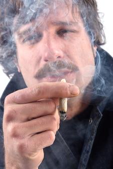Retrato de um homem fumando tabaco mentiroso no fundo branco