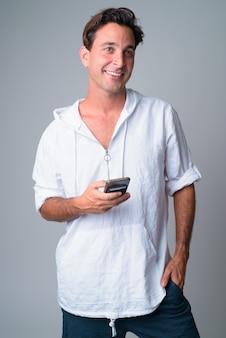 Retrato de um homem hispânico bonito feliz pensando enquanto usa o telefone