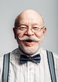 Retrato de um homem idoso sorridente de gravata borboleta e óculos. idoso maduro