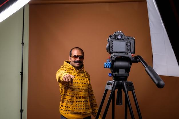 Retrato de um homem indiano com bigode e óculos escuros durante o vlog