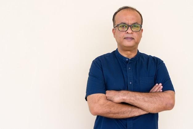 Retrato de um homem indiano com os braços cruzados contra uma parede simples ao ar livre