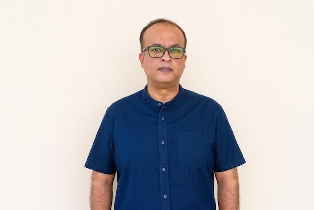 Retrato de um homem indiano contra uma parede simples ao ar livre, olhando para a câmera
