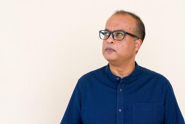 Retrato de um homem indiano pensando contra uma parede simples ao ar livre