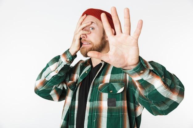 Retrato de um homem infeliz usando chapéu e camisa xadrez, gritando e agarrando a cabeça, em pé isolado sobre um fundo branco