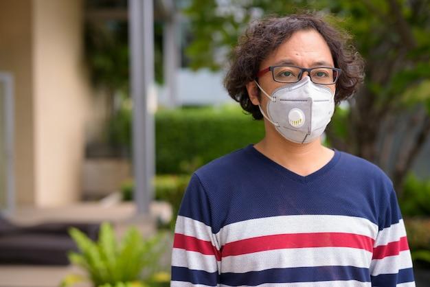 Retrato de um homem japonês com cabelo encaracolado usando máscara para proteção contra surto de coronavírus no jardim da cobertura