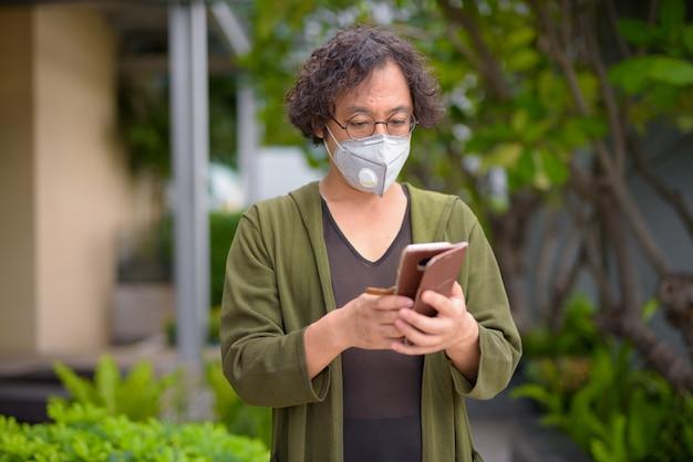 Retrato de um homem japonês com cabelo encaracolado usando máscara para proteção contra surto do vírus corona no jardim do terraço