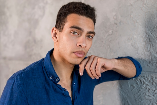 Retrato, de, um, homem jovem, apoiando, parede cinza
