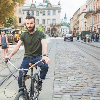 Retrato, de, um, homem jovem, bicicleta equitação, em, cidade
