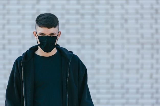 Retrato de um homem jovem, com brincos de argola e roupa preta. ele está usando uma máscara, em um fundo de parede de tijolos
