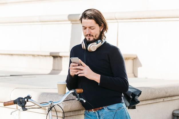 Retrato, de, um, homem jovem, com, headphone, ao redor, seu, pescoço, usando, telefone móvel, em, ao ar livre