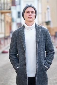 Retrato de um homem jovem e atraente hippie vestindo um casaco cinza, suéter branco e calça jeans preta