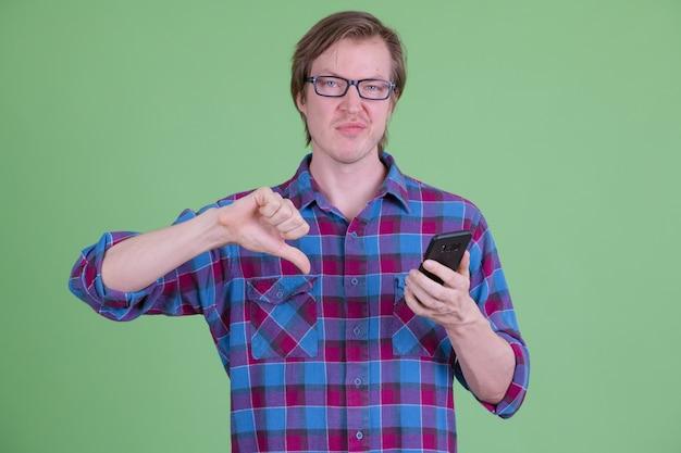 Retrato de um homem jovem e bonito hippie escandinavo com óculos contra chroma key ou parede verde