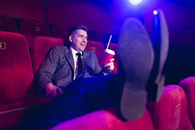 Retrato de um homem jovem e bonito sozinho em uma sala de cinema em um terno de negócio, com os pés no banco da frente e bebendo através de um tubo de um copo vermelho.