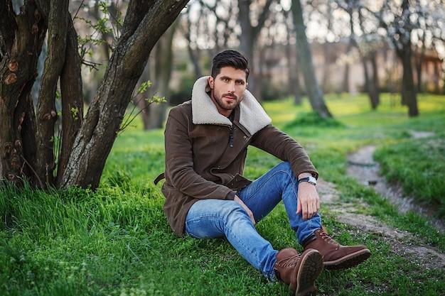 Retrato de um homem jovem e elegante e atraente sentado na grama verde em um bosque ao pôr do sol