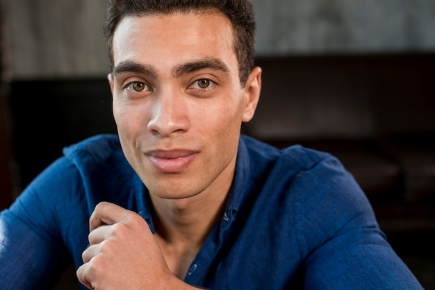 Retrato, de, um, homem jovem, em, camisa azul, olhando câmera