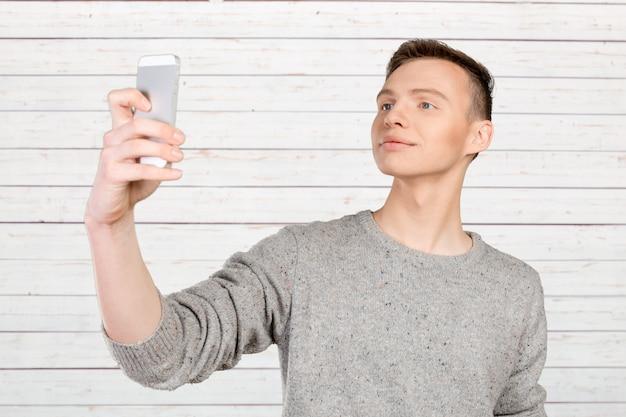 Retrato, de, um, homem jovem, fazendo exame um selfie
