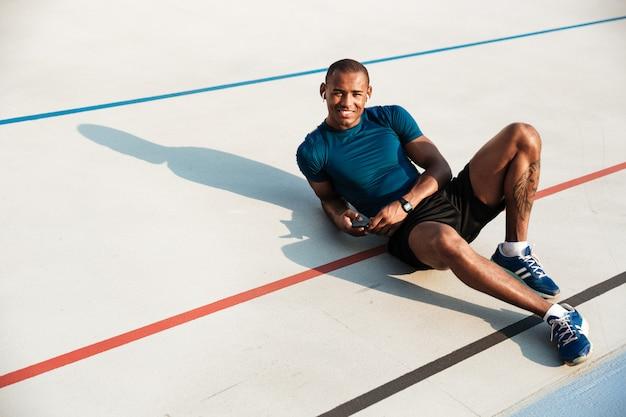 Retrato de um homem jovem feliz africano fitness