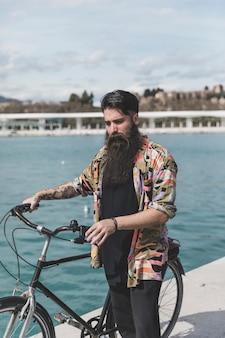 Retrato, de, um, homem jovem, ficar, com, bicicleta, perto, a, costa