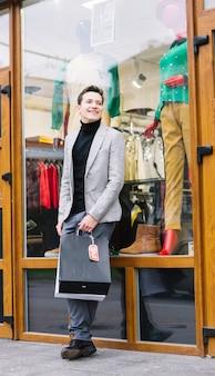 Retrato, de, um, homem jovem, ficar, frente, loja, segurando, bolsas para compras
