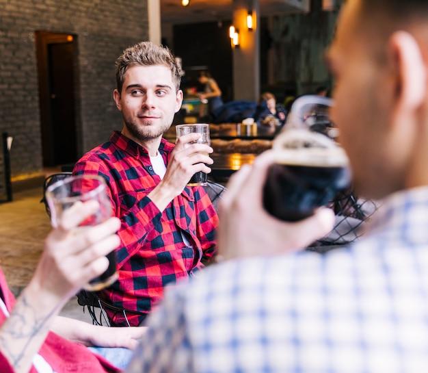 Retrato, de, um, homem jovem, segurando, copo cerveja, sentando, com, seu, amigo