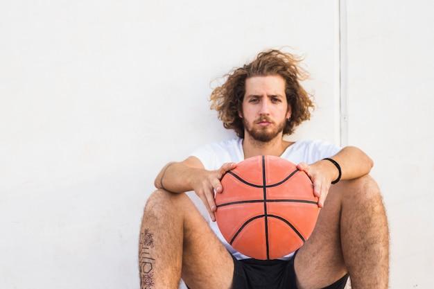 Retrato, de, um, homem jovem, sentando, com, basquetebol