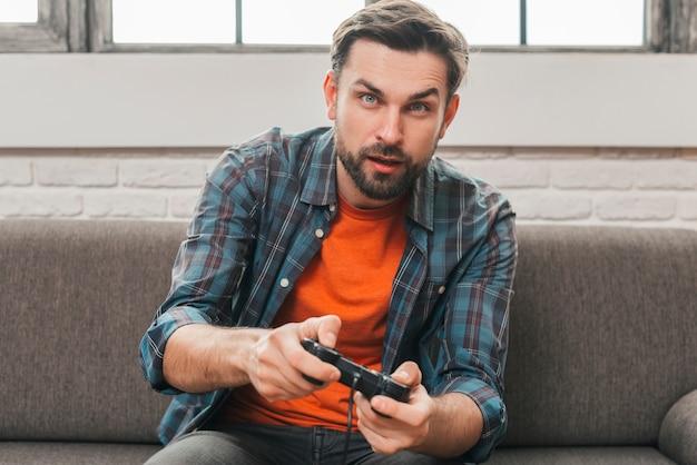 Retrato, de, um, homem jovem, sentar sofá, jogando videogame