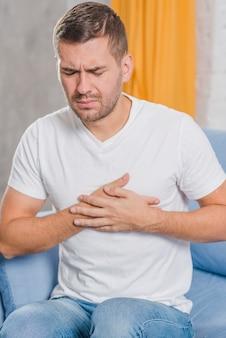 Retrato, de, um, homem jovem, sentar sofá, tendo, peito dor