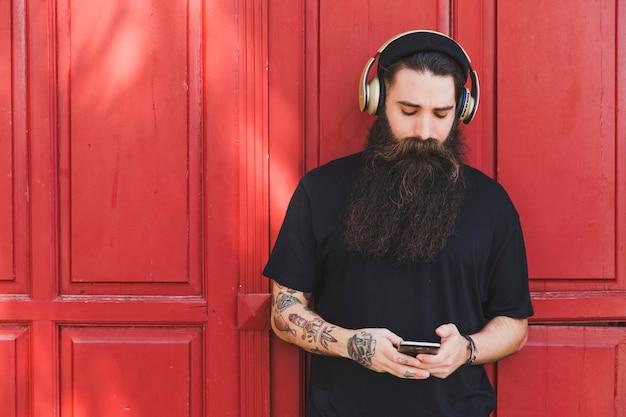 Retrato, de, um, homem jovem, usando, telefone móvel, com, auscultadores, ligado, seu, encabece pé, contra, parede vermelha