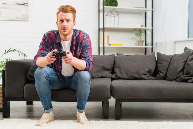 Retrato, de, um, homem jovem, videogame jogando, com, joystick, sentando, em, a, sala de estar