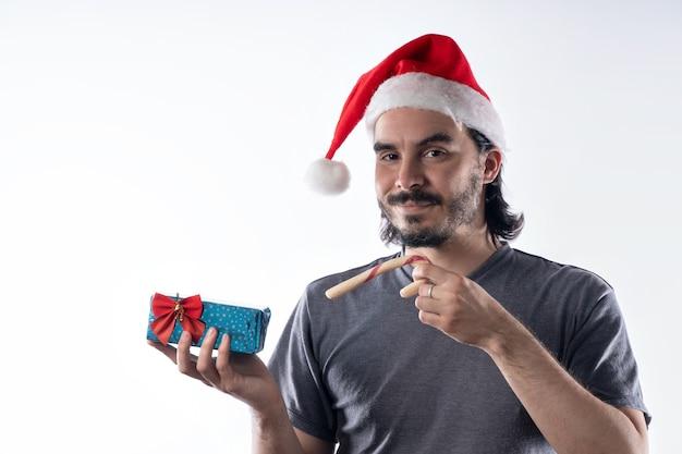 Retrato de um homem latino sorridente com chapéu de papai noel vermelho, olhando para a câmera segurando os presentes de natal
