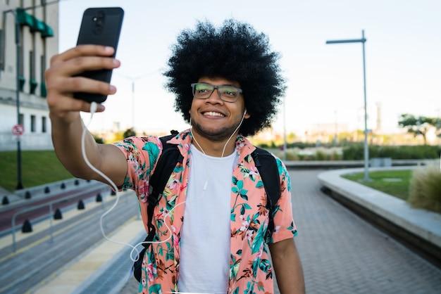 Retrato de um homem latino tirando uma selfie com seu celular enquanto está ao ar livre na rua