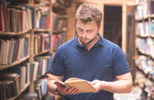 Retrato de um homem lendo um livro em pé em uma biblioteca pública antiga