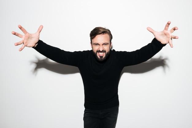 Retrato de um homem louco excitado em pé com as mãos estendidas