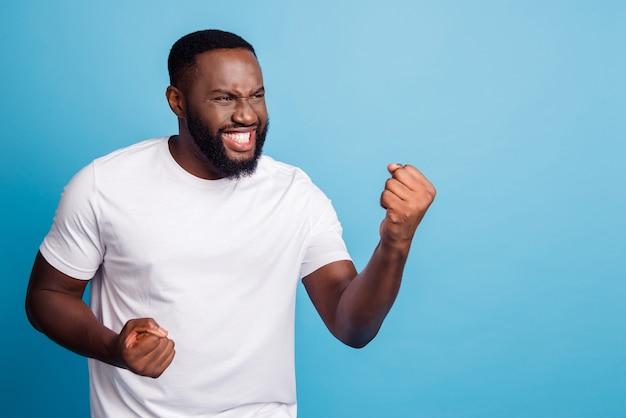 Retrato de um homem louco positivo erguendo os punhos celebrando a vitória sobre o fundo azul