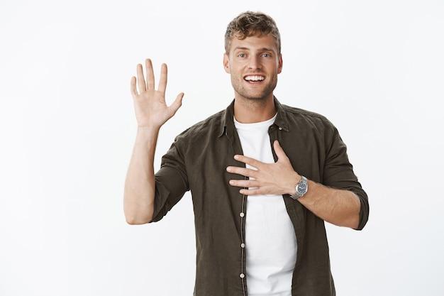 Retrato de um homem maduro, charmoso e carismático, com cabelos louros erguendo a palma da mão e segurando o coração como uma promessa, prometendo e sorrindo na frente