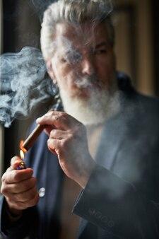 Retrato de um homem maduro de cabelos grisalhos acendendo um charuto enquanto está dentro de casa