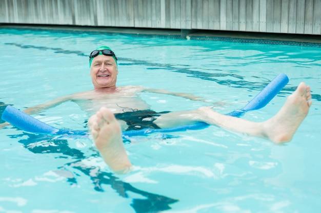 Retrato de um homem maduro e alegre nadando com macarrão de piscina