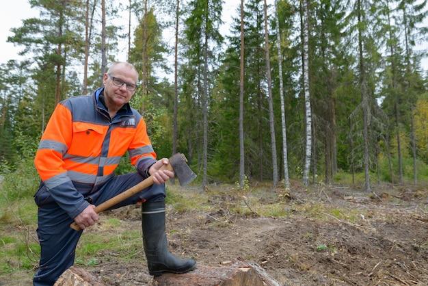 Retrato de um homem maduro e bonito pisando em uma pilha de lenha cortada enquanto segura um machado na floresta