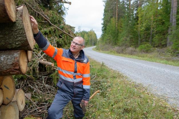 Retrato de um homem maduro e bonito verificando a madeira picada com um buraco no centro enquanto segura o machado