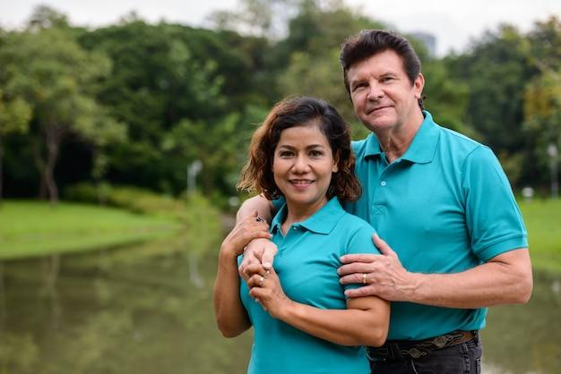 Retrato de um homem maduro e uma mulher asiática madura como um casal multiétnico, juntos e apaixonados no parque ao ar livre