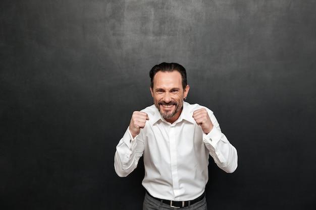 Retrato de um homem maduro feliz vestido de camisa comemorando