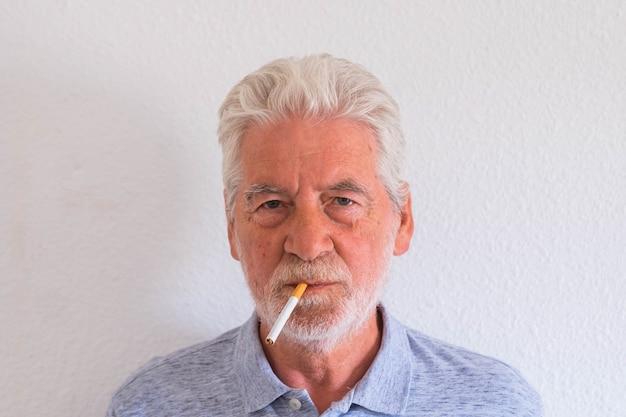 Retrato de um homem maduro ou idoso aposentado fumando e olhando para a câmera com fundo branco - má decisão tentando sair dela